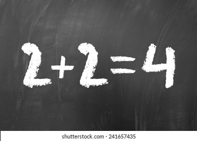 2 plus 2 equals 4 simple math problem solved on a school blackboard