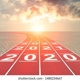 From 2020 into future concept with numbers on running track against sunset desert landscape