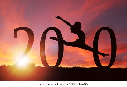 2020 New Year silhouette of a girl dancing during golden sunrise or sunset with copy space.