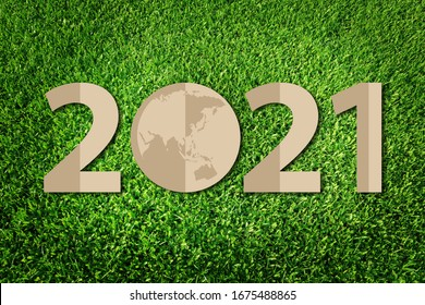 2021 Happy new year greeting card.  Paper art style of eco on green grass background.