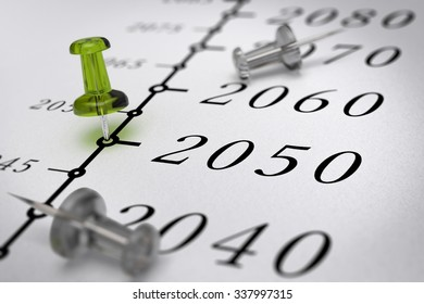 21st Century timeline over paper background with green pushpin pointing the year 2050, blur effect, conceptual image.