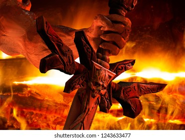 3d illustration of a demon hand with sharped nails holding a skull engraved sword close up view on fire background.