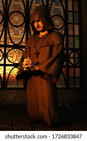 3D illustration of hooded monk kneeling in prayer in front of stained glass