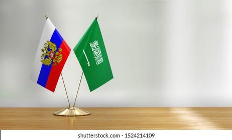 3d illustration. Saudi Arabia and Russian flag pair on a desk over defocused background