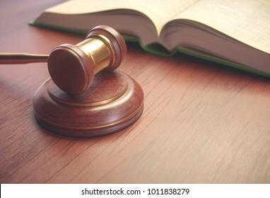 3D illustration. Wooden judge hammer with golden details and a legislation book beside.
