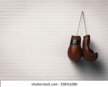 3d rendered boxing gloves hanging on white brick wall background