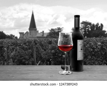3D rendering of a bottle and a glass of fictitious Bordeaux red wine on a table with a chateau in the background