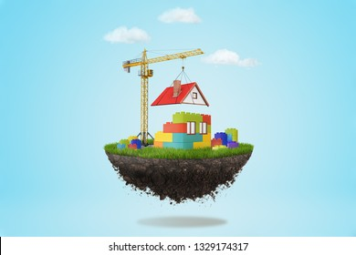 3d rendering of a building crane putting a roof on lego house on a piece of land in the air on blue sky background. Future and technology. Building and construction. Management and success
