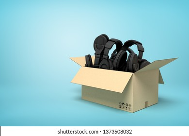 3d rendering of cardboard box full of black headphones on blue background. Music store. Shopping with audiophile. Melomaniac basic needs.