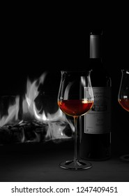 3D Rendering showing a still life with a bottle of red wine and glasses with a fireplace in the background