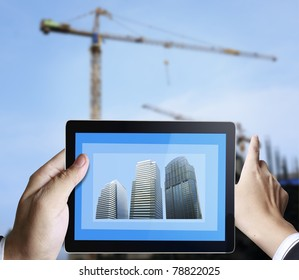 3d touchpad ,hand holding a touchpad pc with the construction of buildings