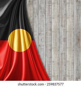 Aboriginal Australia  flag fabric and wood background