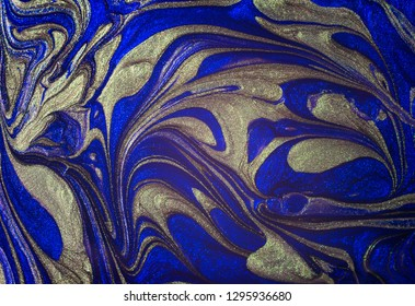 Abstract background. Close-up of blue and golden color nail polish
