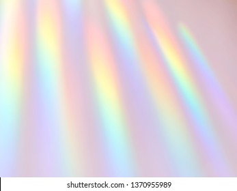Abstract background of rainbow slanted rainbow light rays on solid mauve pink background.