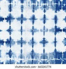 Abstract batik tie dyed fabric of indigo color on white cotton. Hand painted tie-dye fabrics. Shibori dyeing