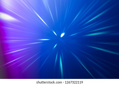 ABSTRACT DARK BACKGROUND WITH BRIGHTLY SHINING RAYS, SPEED LIGHT LINES ON BLUE AND PURPLE GRADIENT PATTERN