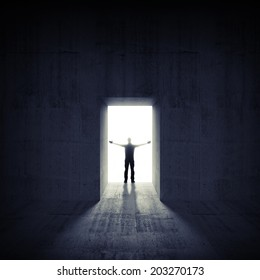 Abstract dark concrete interior with glowing door and man silhouette