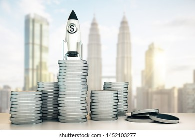 Abstract dollar rocket on silver coins stack. Blurry Kuala Lumpur city background. Startup and venture capital concept. 3D Rendering