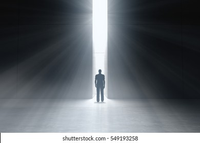 Abstract man in dark concrete interior with glowing doorway and God light rays coming in. Business Concept. 3d rendering