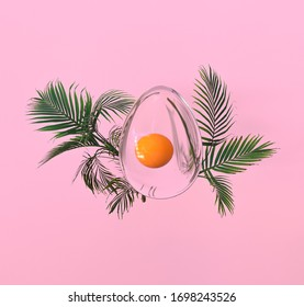 Abstract transparent easter egg composition with palm leaves on pink background. 3d illustration.