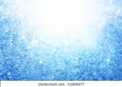 Abstract winter background - blue frozen window with bright light and stars