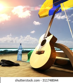 Acoustic guitar near the deck chair under umbrella on the beach at sunset