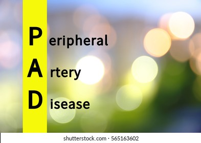 Acronym PAD as Peripheral artery disease. Blurred lights visible on the background.