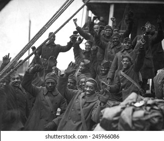 African Americans, members of 369th Colored Infantry, wave from a troop ship as they arrive back in New York City. The regiment was nicknamed the Harlem Hellfighters and the Black Rattlers. Ca. 1919.