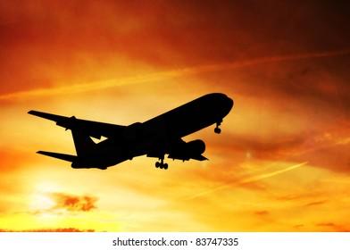 Airplane landing before sunset