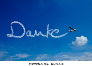 Airplane painting the German word Danke (Thanks) in the sky