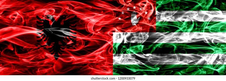 Albania vs Abkhazia, Abkhazian smoke flags placed side by side. Thick colored silky smoke flags of Albanian and Abkhazia, Abkhazian