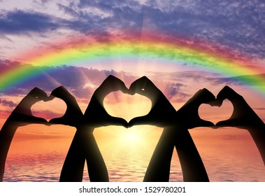 Altruism concept. Three pairs of hands show a heart symbol on a rainbow background