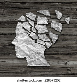 Alzheimer patient medical mental health care concept as a sheet of torn crumpled white paper shaped as a side profile of a human face on wood as a symbol for neurology and dementia or memory loss.