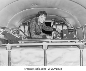 Amelia Earhart (1897-1937), checking equipment on her airplane. Ca. 1937.