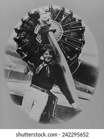 Amelia Earhart (1897-1937), posting in front of the propeller of her Lockheed L-10E Electra on July 8, 1937, on land during a stop in her final round-the-world flight which began from Miami, Florida.