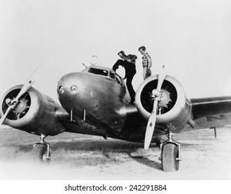 Amelia Earhart on wing of her Lockheed L-10E Electra airplane. At right is Fred Noonan, her navigator entering the cockpit, at a stop in Puerto Rico during their attempt to fly around the world. 1937.