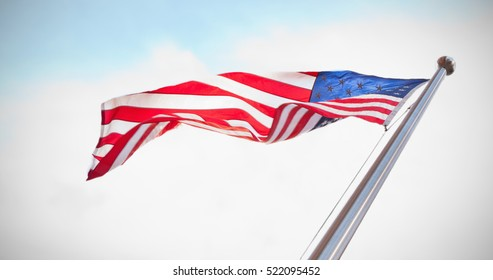 American flag against blue sky with clouds