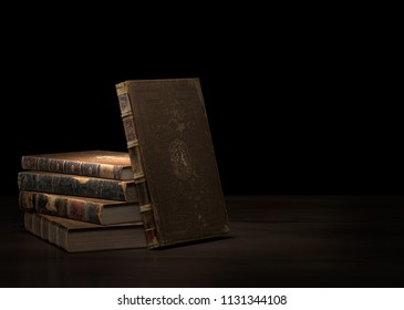 Ancient books pile on wooden surface.