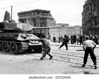 Anti-Communist riots in East Germany: An East Berliner throws stones at a Russian tank during the first violent resistance.