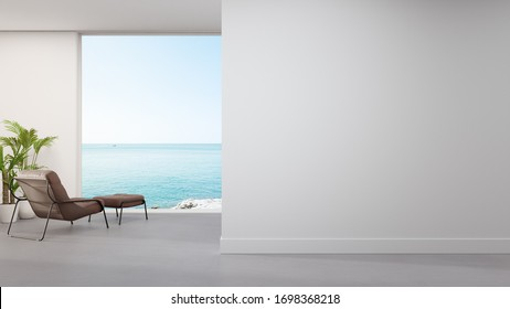 Armchair on concrete floor of large living room in modern house or luxury hotel. Minimal home interior 3d rendering with beach and sea view.