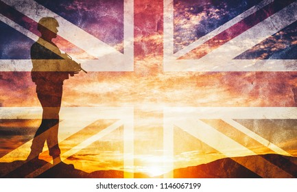 Armed soldier with rifle and British flag standing and looking on horizon. Silhouette at sunset. War, army, military, guard.