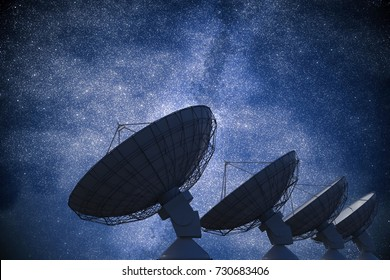 Array of satellite dishes or radio antennas against night sky. Space observatory. 3D rendered illustration.
