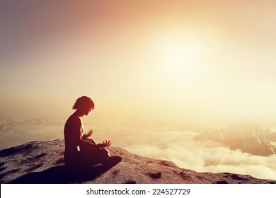 Asian man meditates in yoga position in high mountains above clouds at sunset. Unique concept of meditation, spirituality, balance, harmony in life.