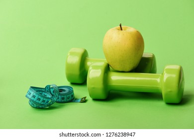 Athletics and weight loss concept. Dumbbells in green color, twisted measure tape and fruit on green background. Tape measure in cyan blue color near barbells and juicy apple. Sports regime symbols