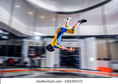 Attraction . Men show stunts in a wind tunnel . Indoor skydiving sportsmens fly in tunnel . Simulator of free fall.