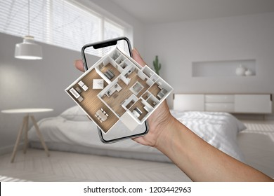 Augmented reality concept. Hand holding smartphone with AR application used to simulate 3d pop-up interactive house maps to life, modern blurred bedroom in the background, 3d illustration