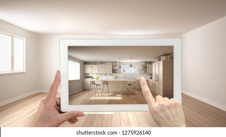 Augmented reality concept. Hand holding tablet with AR application used to simulate furniture and design products in empty interior with parquet floor, modern white kitchen, 3d illustration