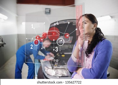 Auto mechanic with customer looking at futuristic interface with car diagram