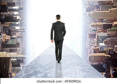 Back view of businessman in suit walking on concrete walkway. Abstract rotated city background. Success concept