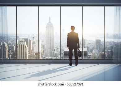 Back view of man with briefcase in modern interior with city view, looking into the distance. Research concept. 3D Rendering